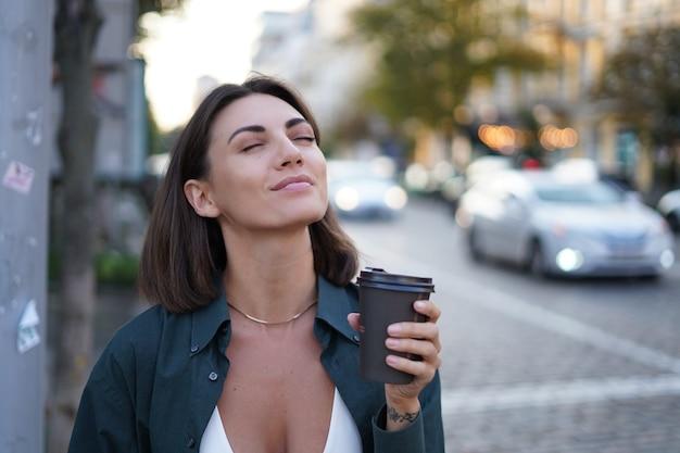 Mulher caucasiana com uma xícara de café ao ar livre rua da cidade feliz sorrindo