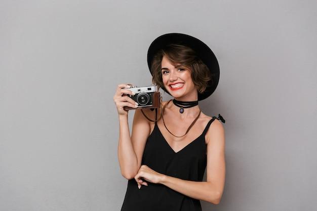 Mulher caucasiana com vestido preto e chapéu fotografando na câmera retro, isolada sobre uma parede cinza