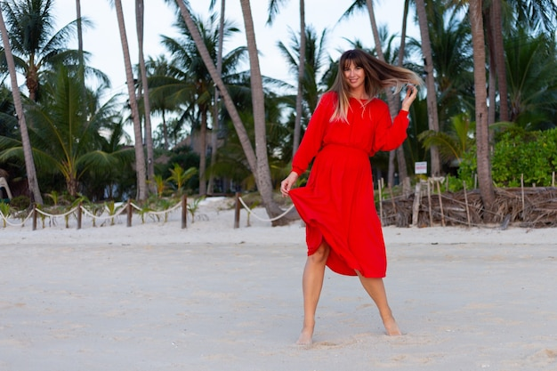 Mulher caucasiana com vestido vermelho de verão e clima romântico feliz na praia tropical de areia branca ao pôr do sol
