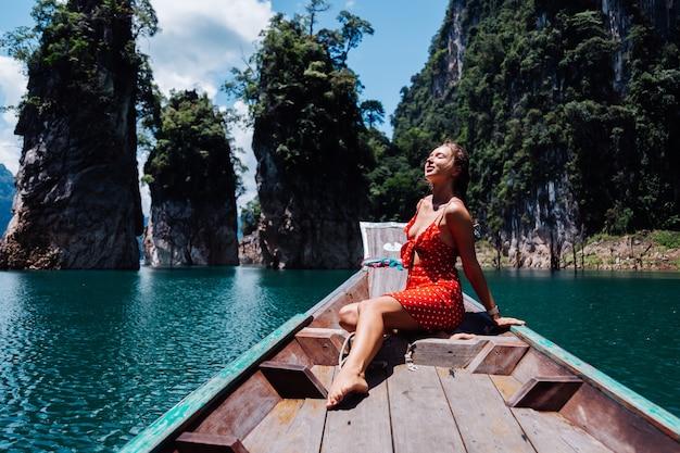 Mulher caucasiana com vestido vermelho de verão em um barco tailandês asiático de férias, viajar pela tailândia