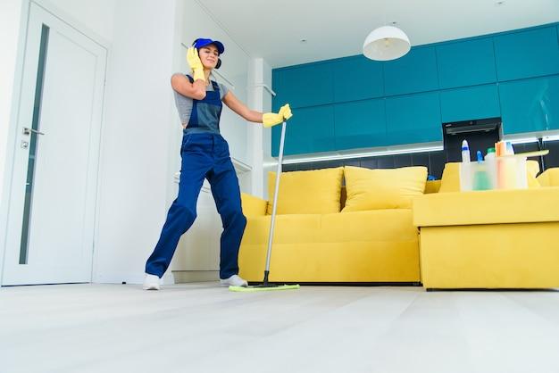 Mulher caucasiana como um limpador profissional em fones de ouvido, limpando o chão com a esfregona e ouve música em casa.