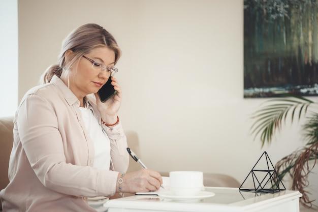 Mulher caucasiana concentrada com cabelo loiro e óculos, escrevendo algo no livro e falando ao telefone