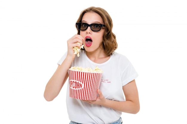 Mulher caucasiana concentrada segurando pipocas usando óculos 3d
