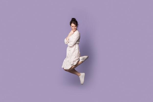 Mulher caucasiana confusa com um vestido de verão pulando na parede violeta do estúdio e olhando para a câmera
