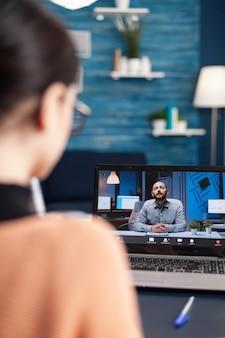 Mulher caucasiana, conversando com seu professor de matemática durante a conferência de videochamada da universidade usando laptop cumputer. aluno trabalhando em uma aula de comunicação enquanto está sentado na mesa da sala de estar