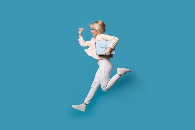 Mulher caucasiana correndo com um presente na parede azul do estúdio