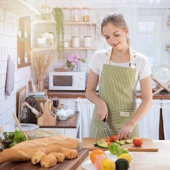 Mulher caucasiana, cozinhar alimentos na cozinha.