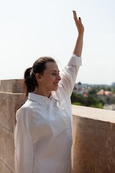 Mulher caucasiana cumprimentando pessoas em pé no terraço da torre