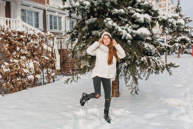 Mulher caucasiana dançando num lindo chapéu de malha. retrato de corpo inteiro ao ar livre de uma senhora de cabelos compridos feliz em calças rasgadas brincando perto de uma árvore com neve.