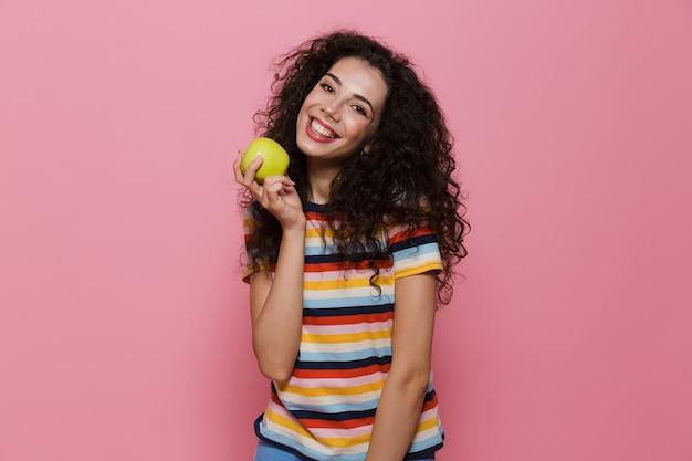 Mulher caucasiana de 20 anos com cabelo encaracolado sorrindo e segurando uma maçã verde isolada na rosa