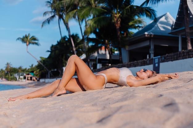 Mulher caucasiana de biquíni e óculos escuros em uma praia tropical