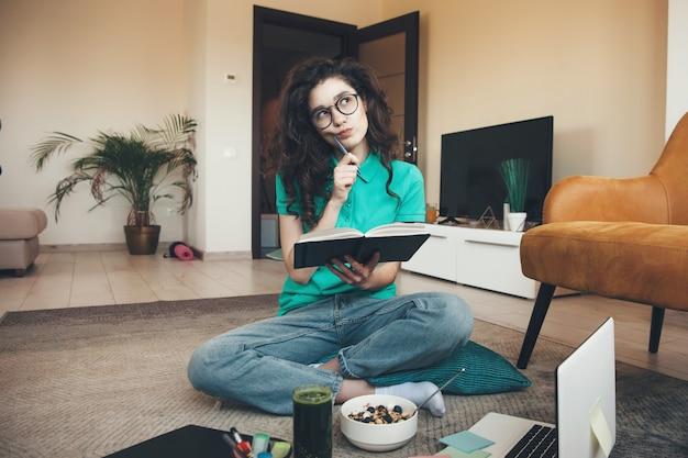 Mulher caucasiana de cabelos cacheados com óculos, comendo cereais com suco de vegetal fresco, fazendo a lição de casa no chão, usando um livro e um laptop