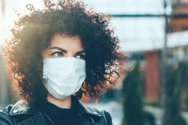 Mulher caucasiana de cabelos cacheados usando uma máscara anti-gripe enquanto posava do lado de fora na frente de um prédio