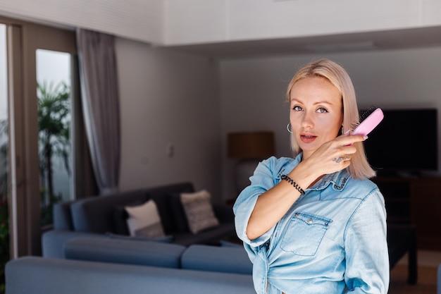 Mulher caucasiana de cabelos curtos, bonita, loira, com jaqueta jeans, escovando os cabelos com uma escova rosa em casa