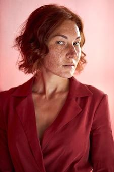 Mulher caucasiana de cabelos curtos olhando seriamente para a câmera isolada no estúdio, usando um vestido vermelho