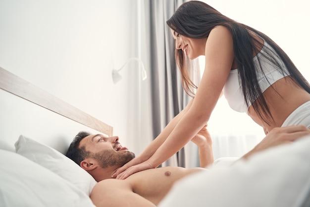Mulher caucasiana de cabelos escuros, alegre, de cueca, brincando com seu jovem marido na cama