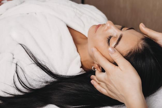 Mulher caucasiana de cabelos negros fazendo uma massagem facial anti-envelhecimento no salão spa