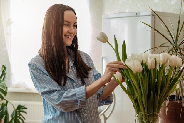 Mulher caucasiana de camisa azul cuidando de tulipas brancas em um vaso