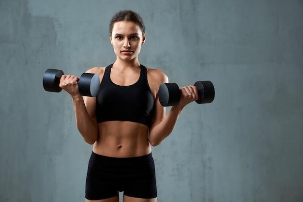 Mulher caucasiana de fitness treinando com halteres