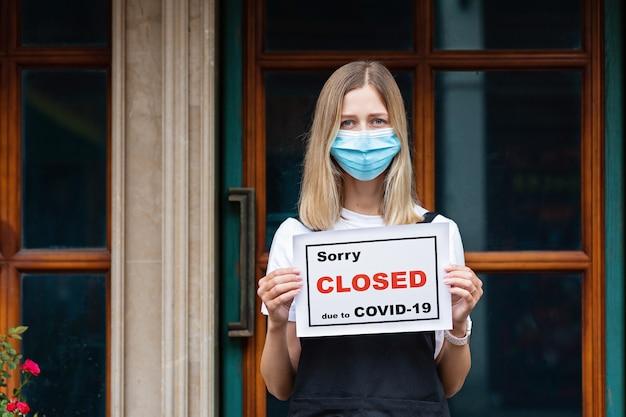 Mulher caucasiana de garçonete usando máscara médica detém lamento, estamos fechados. pandemia do coronavírus
