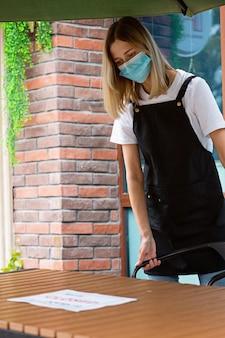 Mulher caucasiana de garçonete usando máscara médica e desculpe, estamos fechados. pandemia do coronavírus