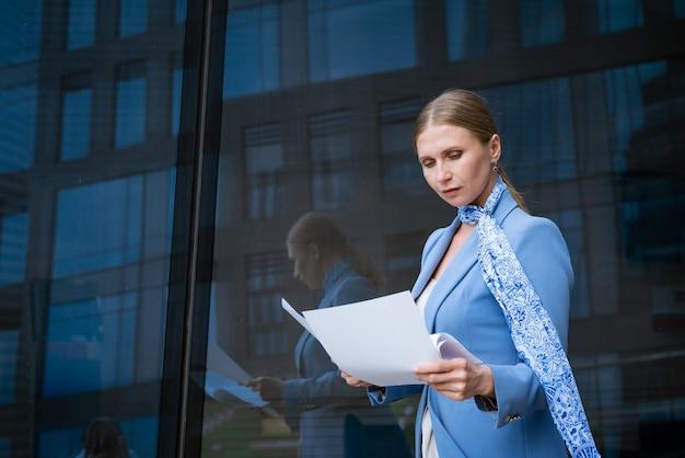 Mulher caucasiana de jaqueta azul e negócios bem-sucedidos segurando documentos perto de prédio de escritórios