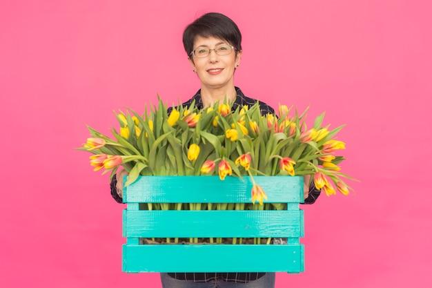 Mulher caucasiana de meia idade com caixa de tulipas na parede rosa.