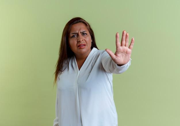Mulher caucasiana de meia-idade descontente descontente mostrando gesto de parada isolado na parede verde oliva