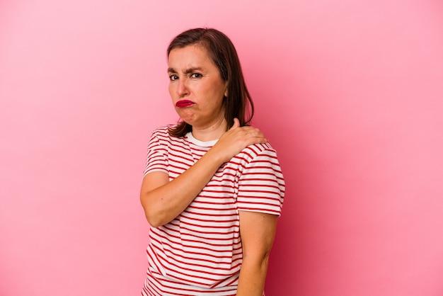 Mulher caucasiana de meia idade isolada em um fundo rosa, tendo uma dor no ombro.
