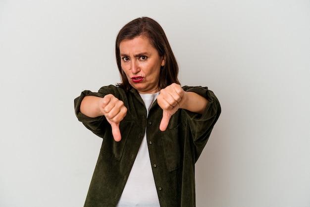 Mulher caucasiana de meia-idade, isolada no fundo branco, mostrando o polegar para baixo e expressando antipatia.