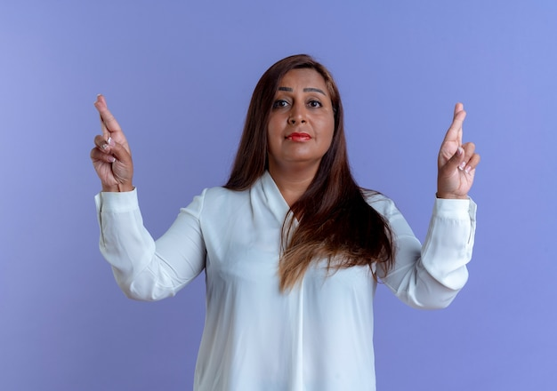 Mulher caucasiana de meia-idade preocupada e preocupada cruzando os dedos