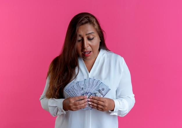 Mulher caucasiana de meia-idade preocupada, segurando e olhando para o dinheiro