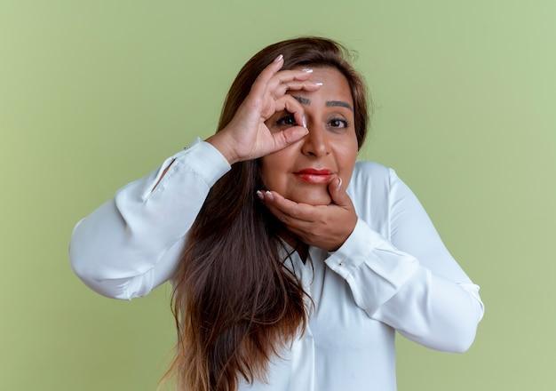 Mulher caucasiana de meia-idade satisfeita mostrando um gesto de olhar e colocando a mão no queixo