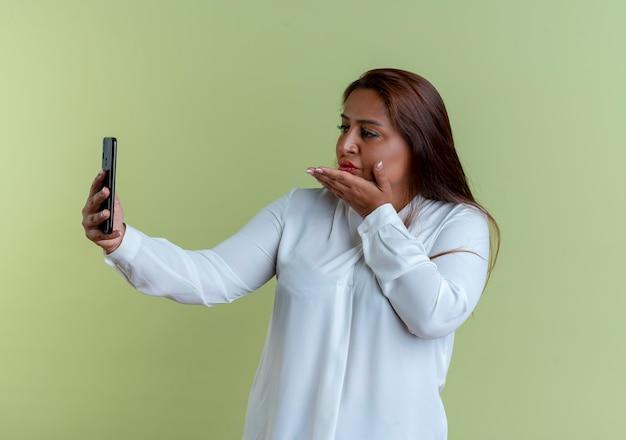Mulher caucasiana de meia-idade satisfeita tirando uma selfie e mostrando um gesto de beijo