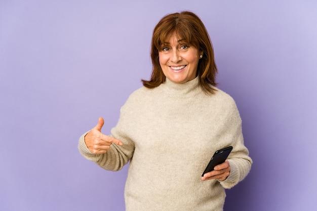 Mulher caucasiana de meia-idade segurando um fone apontando com a mão para um espaço de cópia de camisa, orgulhosa e confiante