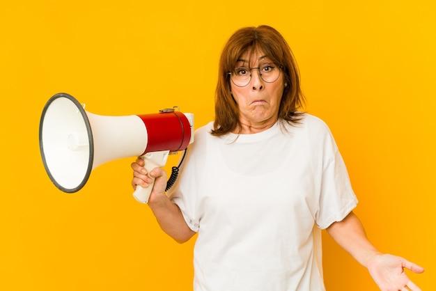 Mulher caucasiana de meia idade segurando um megafone encolhe os ombros e abre os olhos confusos.