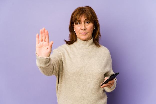 Mulher caucasiana de meia-idade, segurando um telefone em pé com a mão estendida, mostrando o sinal de pare, impedindo você.