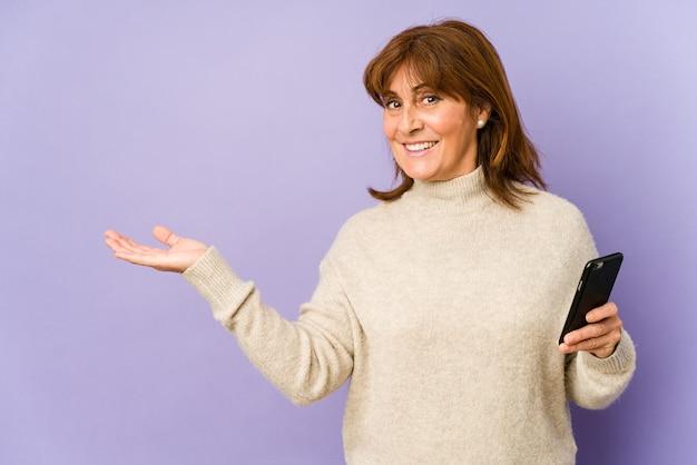 Mulher caucasiana de meia-idade segurando um telefone mostrando um espaço de cópia na palma da mão e segurando a outra mão na cintura.