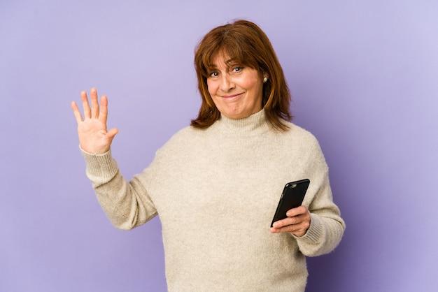 Mulher caucasiana de meia idade segurando um telefone sorrindo alegre mostrando o número cinco com os dedos.