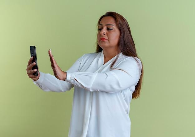 Mulher caucasiana de meia-idade tirando uma selfie e mostrando um gesto de parar
