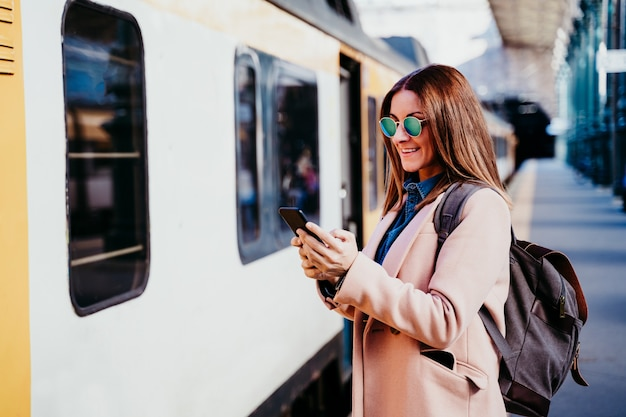 Mulher caucasiana de mochileiro feliz na plataforma na estação de trem usando telefone celular. conceito de viagens