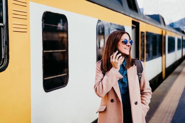 Mulher caucasiana de mochileiros feliz na plataforma na estação de trem, falando no celular. conceito de viagens