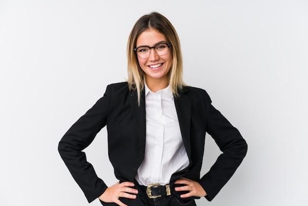 Mulher caucasiana de negócios jovem confiante, mantendo as mãos nos quadris.