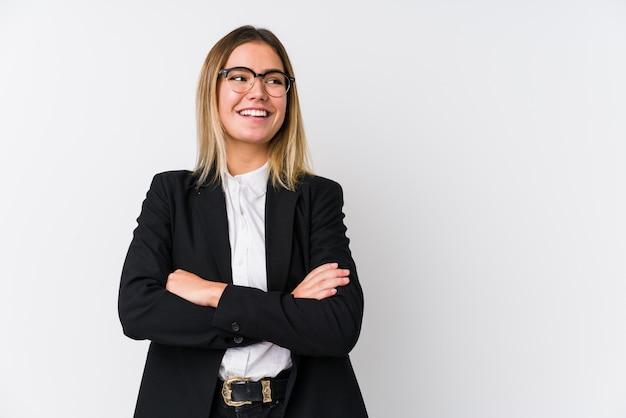 Mulher caucasiana de negócios jovem sorrindo confiante com braços cruzados.