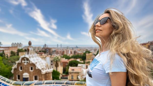 Mulher caucasiana de óculos escuros com vista de barcelona ao fundo, espanha