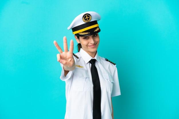 Mulher caucasiana de piloto de avião isolada em fundo azul feliz e contando três com os dedos