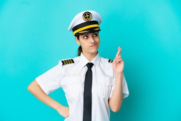 Mulher caucasiana de piloto de avião isolada em um fundo azul com os dedos se cruzando e desejando o melhor