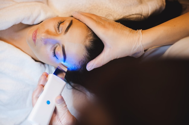 Mulher caucasiana deitada com os olhos fechados enquanto realiza procedimentos de spa no rosto usando aparelho de ultrassom