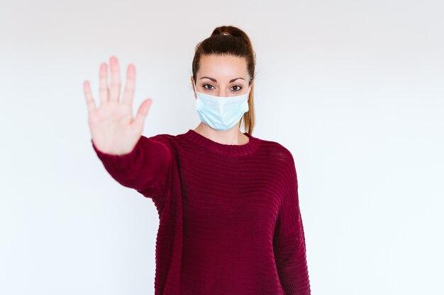 Mulher caucasiana, dentro de casa, usando máscara protetora. fazendo um sinal de stop com a mão. conceito de vírus corona covid-19