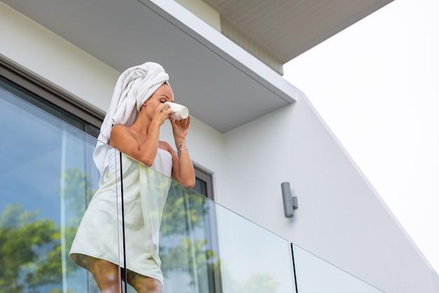 Mulher caucasiana depois do banho de toalha fica na varanda da villa e bebe café ou chá. um começo perfeito do dia. mulher calma e relaxada encontra o novo dia